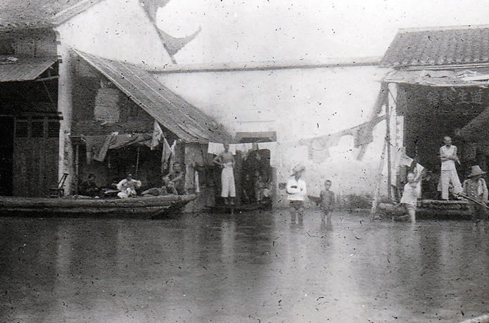Flooded houses in Hanyang with people leaving in boats.