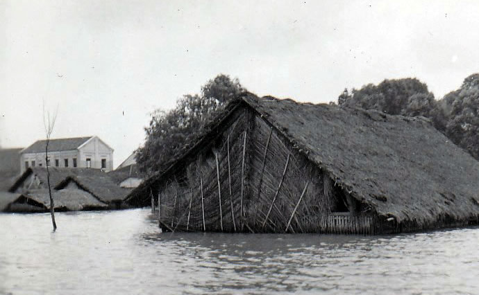 Flooding covers all but the roof of a mat house